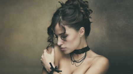 necklaces: young beautiful woman with dark wavy hair pulled into a bun portrait, studio shot