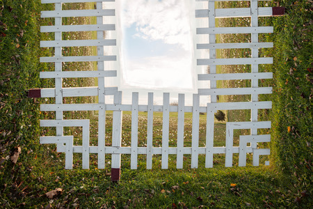 photo manipulation: white wooden fence on field with sky in background, bend photo manipulation Stock Photo