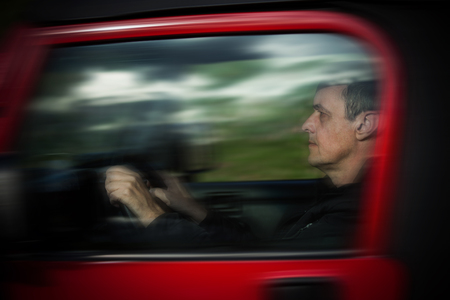 car side view: man drive his car side view  through the glass reflection of trees and sky in glass motion blur