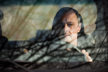 man front view: man in his car behind wheel front view through the glass reflection of trees and sky in glass