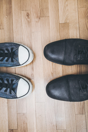 choose person: men black leathe shoes and blue worn sneakers on parquet from above Stock Photo