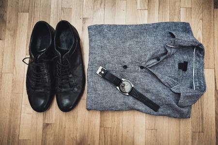 wristlet: men black leather shoes, gray cotton shirt and wristlet watch on parquet, above view