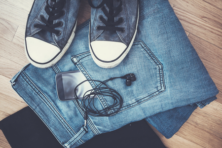 life style: men pair of blue jeans, black t-shirt, sneakers, smartphone and earphones on parquet from above