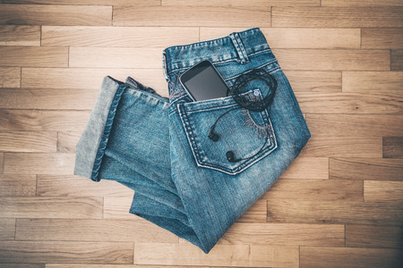 handphone: blue jeans smart phone and earphones on wooden background Stock Photo