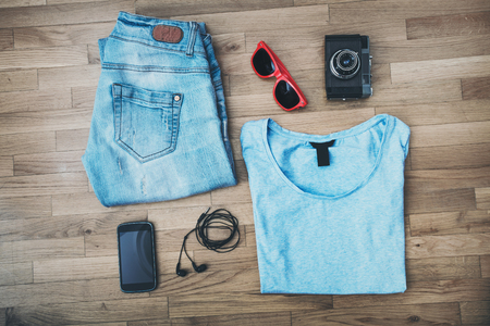 handphone: casual girl outfit background, blue jeans, t-shirt, smart phone, earphones, old camera and sunglasses
