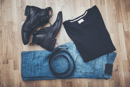 black t shirt: men black leather shoes and blue worn jeans, t-shirt and belt on parquet from above