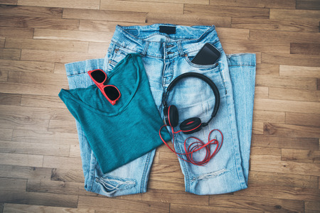 girl casual every day outfit, worn blue jeans, t-shirt, sunglasses, smart phone and headphones
