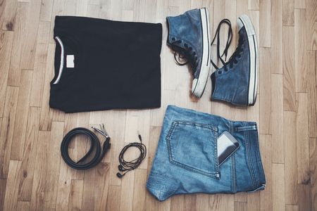 casual men: men casual outfit background, black t-shirt, worn blue jeans and sneakers, smart phone, earphones and belt, on parquet above view
