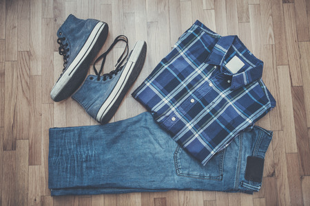 plaid shirt: men casual outfit background, worn blue jeans, sneakers and plaid shirt Stock Photo