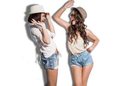ropa de verano: alegres dos mujeres jóvenes en ropa de verano han jeaans diversión que lleva pantalones cortos gafas de sol y sombreros Foto de archivo