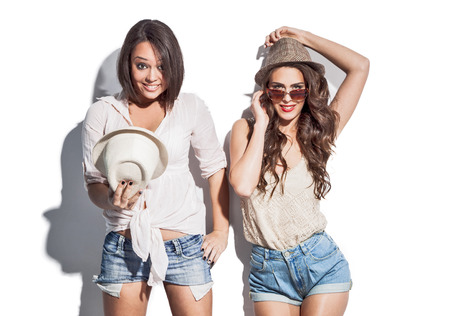 cheerful two young women in summer clothes have fun wearing jeaans shorts sunglasses and hats Stock Photo