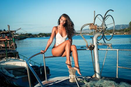 barca da pesca: giovane donna abbronzata in bikini sulla vecchia barca da pesca in posa colpo di corpo pieno Archivio Fotografico