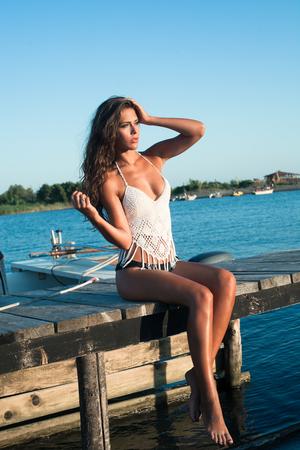 junge Frau genießen in der Sommersonne am Bootssteg auf See sonnigen Sommertag Ganzkörperfoto Standard-Bild