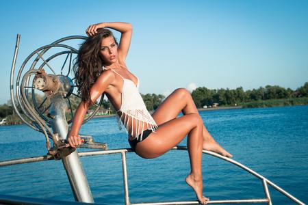 junge gebräunte Frau im Bikini auf dem alten Fischerboot Ganzkörperfoto posieren