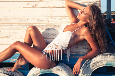 tiers: tanned young woman in bikini and white top lie on tiers on sandy summer beach by wooden house
