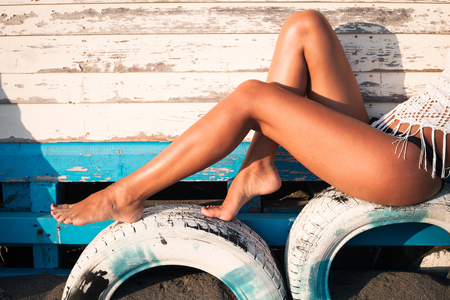 tanned woman legs on tires by wooden house at sea sunny summer day, side view