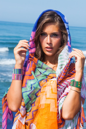 vacation summer: tanned young beach fashion woman portrait with  colorful sarong and bracelets  at sea beach sunny summer day Stock Photo