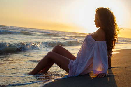 sea beach: young woman sit at sand beach in long shirt enjoy in sunset bay the sea, side view full body shot