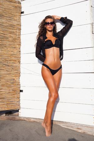 contrast: tanned attractive young woman in black bikini and shirt in front of white wooden background on beach sunny summer day full body shot