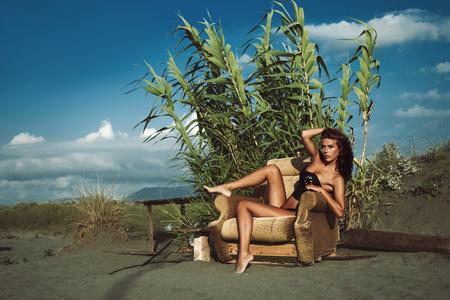 cuerpo femenino: atractiva mujer joven en bikini y encima sentarse en el sillón en la playa de arena caliente soleado día de verano, el cuerpo un disparo