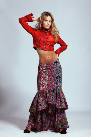 young woman in red leather jacket and floral print skirt, studio shot photo