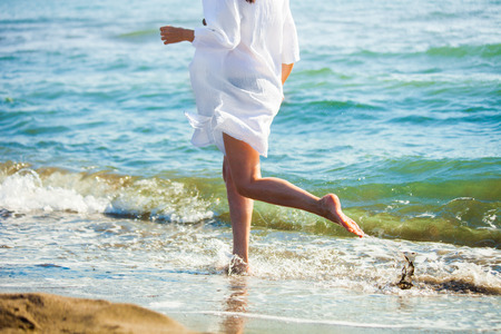 lower body: woman run at sand beach by the sea, lower body, sunny summer day