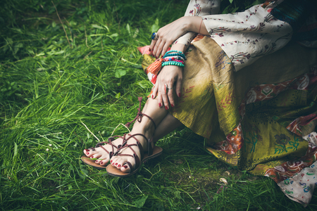 woman legs  on grass in strap flat sandals and boho style silky  dress  with lot of bracelets on hands Stockfoto