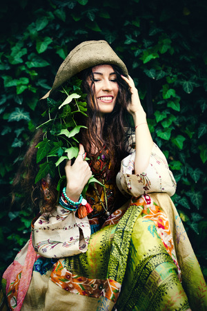 silky hair: smiling young woman in silky boho style dress and ivy in hair and hat sit in garden summer day Stock Photo