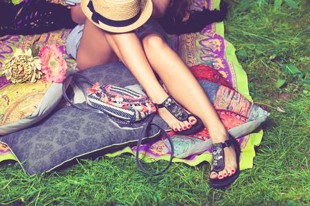 donna piedi su erba in sandali estivi piatti magre sul cappello cuscini giacevano sulle gambe dall'alto