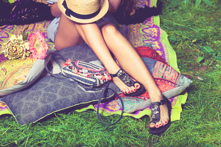 woman feet on grass in flat summer sandals lean on pillows  hat lay on legs from above Stockfoto