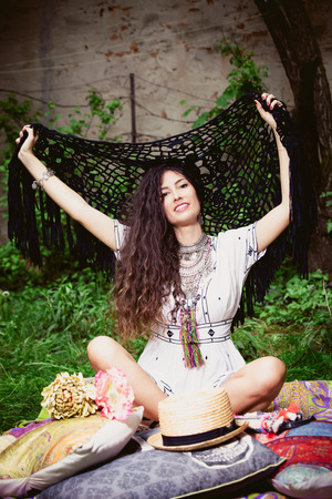 arms open: smiling young woman in boho style clothes sit in garden on grass with arms open holding crocheted scarf full body shot Stock Photo