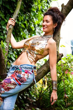 bollos: mujer joven con el pelo sonriendo en bollo en la ropa del estilo boho plantean en el día de la rama de árbol de té en el jardín Foto de archivo