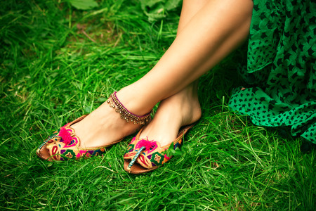 beautiful ankles: female legs on grass in leather ethnic boho summer sandals
