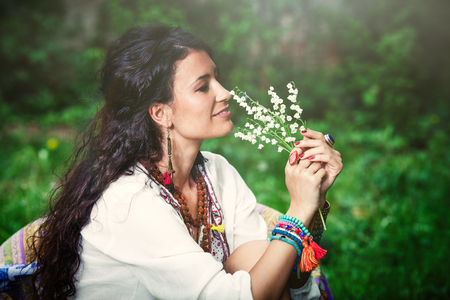 side shot: smiling young woman in boho style clothes hold lily of the valley side shot outdoor closeup