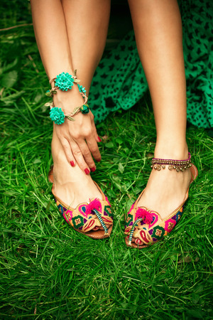 indian style sitting: female legs on grass in leather ethnic boho summer sandals