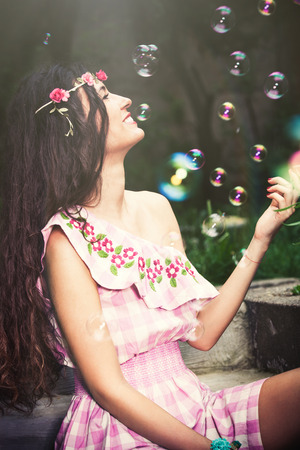 backyard woman: smiling young woman in romantic summer dress enjoy in bubbles outdoor in backyard summer day Stock Photo