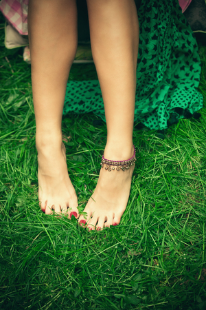 woman feet: barefoot woman feet on grass with ankle bracelet shot from above