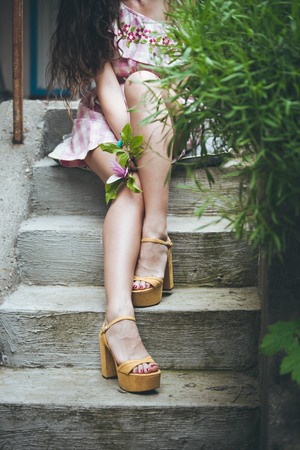 lower body: young woman legs in high heel sandals on stairs in garden hold flower in hand