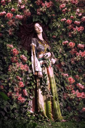 giovane donna in abito lungo sognare in giardino Photo composito