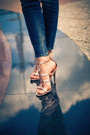 woman legs in high heel sandals stand on marble pavement