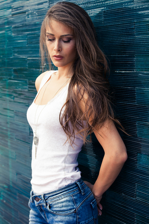 tiled wall: young woman in white t-shirt and blue jeans outdoor portrait in the city lean on blue tiled wall