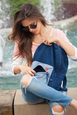 ropa de verano: mujer joven en ropa casual y jeans con gafas de sol de tomar un descanso durante el día de verano en la fuente de la ciudad