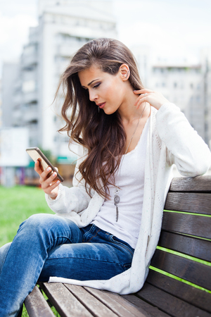women in jeans: young woman sit on wooden bench in city park with smartphone in hand Stock Photo