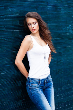 tiled wall: young urban woman in blue jeans and white sleeveless t-shirt lean on tiled wall outdoor shot in the city