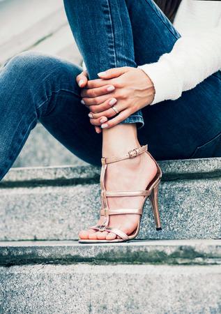 jolie pieds: jeune femme dans les chaussures à talons hauts et un jean bleu sur le tir en plein air escaliers Banque d'images