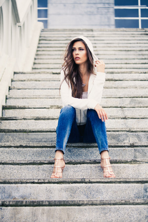 girl sit: urban young woman sit on stairs in blue jeans high heel sandals and white sweater with hood full body shot