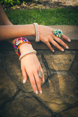 finery: closeup of female hands with colorful  ring and bracelets on stone