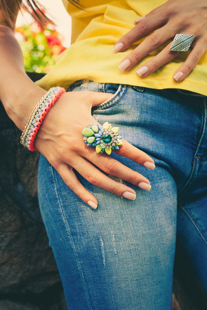 finery: woman hand on blue jeans with big colorful ring and bracelet summer trendy bijou