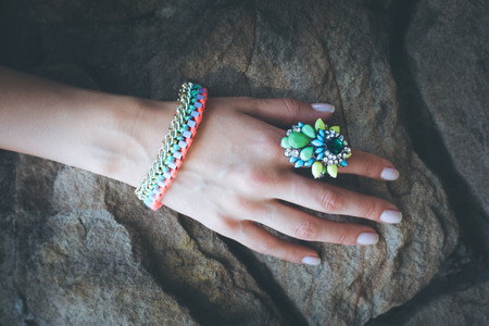 finery: closeup of female hand with colorful  ring and bracelet on stone