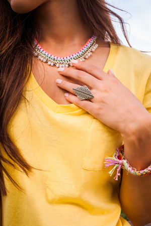female  hand and nack  with large ring and colorful necklace closeup outdoor shot Stock Photo